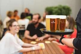 Bei den Ottakringer Braukultur-Wochen freut sich eine Gruppe am Tisch auf die Ottakringer Biere, die im Vordergrund auf einem Tablett herangetragen werden