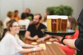 Rechts vorne ein Tablett mit mehreren Gläsern mit Ottakringer Bier, dahinter verschwommen Gäste an Tischen