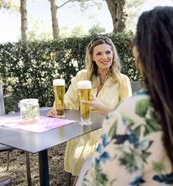 Zwei Frauen, darunter Bierbotschafterin Christa Kummer, stossen im Biergarten mit einem gepflegten Pils an