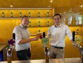 Micke Neureiter und Tobias Frank stossen mir einem Bier vor einer gelben Wand mit Ottakringer Logo und Flaschen an