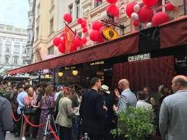 Viele 'schöne und berühmte' Leute vor dem Kameel, über dessen Markisen viele rote Campariballons schweben
