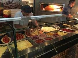 In der offenen Küche des Eatalico gibt ein Pizzabäcker reichlich Mozzarella auf einen bereits mit Tomatensauce bestrichenen Pizzaboden, dahinter sieht man das Feuer im Pizzaofen