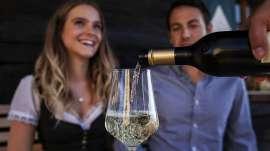 Ein junges paar in Tracht lässt sich Steirischen Junker in ein Glas einschenken