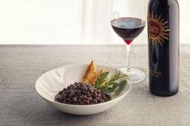 Kalte Suppe von schwarzen Kichererbsen mit Kräutern und Nativem Olivenöl Extra Evo Luce, daneben eine Flasche Luce 2016