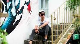 Martin Ho mit Hut sitzt auf einer Treppe