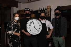 Broadmoar-Küchenchef Johann Schmuck (2.v.l.) mit Sous Chef Christoph Schober und Premierengästen mit einer überdimensionalen Uhr, deren Zeiger auf 5 Uhr zeigen.