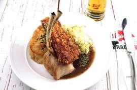 Knuspriges Spanferkel vom Grill mit Kraut und Knödel mit Saft, daneben ein frisch gezapftes Stiegl-Bier