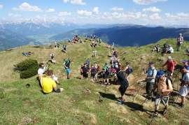 Impressionen vom Stoabergmarsch: Zahlreiche Wanderer auf einer Bergwiese, im Hintergrund Berge