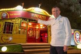 Toni Mörwald in weisser Kochjacke vor dem abendlich erleuchteten Palazzo Glaspalast