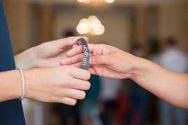 Zwei Hände streifen einer dritten Hand das Eintritts-Gumiband über