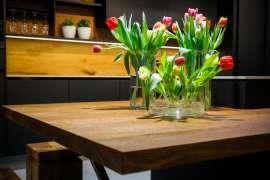 Edles Design: ein eleganter Holztisch, darauf 3 Vasen mit Tulpen, Dahinter eine Kommode mit Kakteen und Weingläsern im Regal
