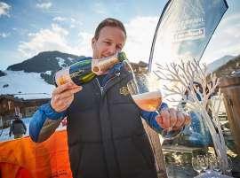Champagner wird unter blauem Himmel im Freien eingeschenkt