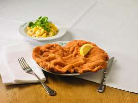 Klassisches Wiener Schnitzel mit Zitronenscheibe und Erdäpfelsalat