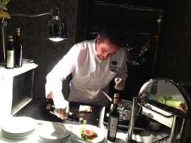 Küchenchef Schartner giest Olivenöl über ein Stück Crepinette