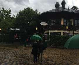 Einige Leute mit Grünen Regenschirmen gehen auf den Eingang des Schweizerhaus zu