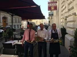 Lotfi Nasr (Inhaber), Peter Dobcak (WKO Gastronomie-Obmann) und Antonio (Kellner der Trattoria) servieren Speisen im Aussenbereich