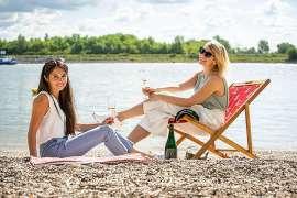 Zwei junge Frauen sitzen an einem Fluss mit alkoholfreiem Wein