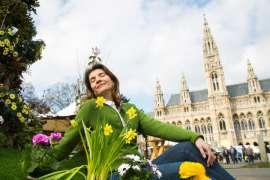 Die Steirer bringen den Frühling: eine junge Frau in grüner Trachtenjacke sitzt vor dem Wiener Rathaus, davor Frühlingsblumen