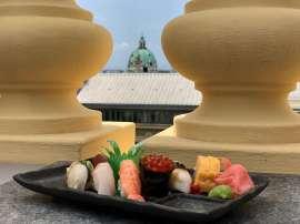 Ein Teller Sushi steht auf der Brüstung, dahinter sieht man die Karlskirche