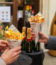 Am mercato Barbaro halten zwei Hände je ein Papierstanizel mit Essen, dahiner zahlreiche Flaschen Moet & Chandon