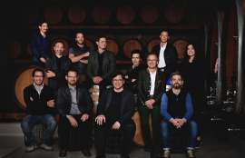 Vertreter der nunmehr 12 STK-Weingüter im Gruppenphoto vor Weinfässern