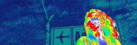 Wärmebildkamera-Photo einer Person vor einem Flughafenschild