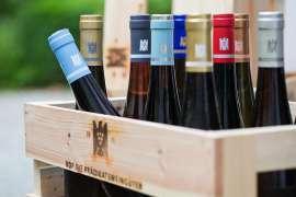 Eine Holzsteige mit VDP-Logo, darin mehrere Flaschen mit bunten Kapseln mit VDP-Logo