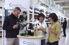 Kunden im LEH verksoten Wein an einem Stand vor vollen Regalen mit Deutschem Wein