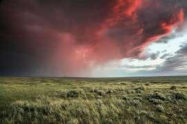Bedrohliche feuerrote Wolken mit Blitzen über einer Wiese