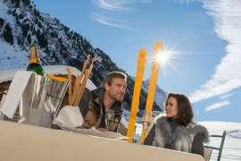 Champagnergenuss auf der Sonnenterrasse, im Hintergrund schneebedeckte Berge unter strahlend blauem Himmel