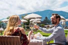 Ein Herr mit Bart und eine blonde Dame stoßen auf der Gastterrasse im Weinmesser  mit Weißwein an, im Hintergrund Berge