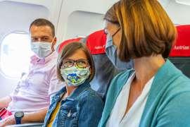 In einem Flugzeug sitzen ein Mann, ein Kind und eine Frau, alle drei mit MNS-Masken