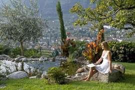 Frau am Weiher mit Blumen, im Hintergrund Algund