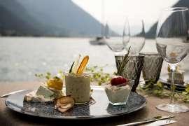 Frühstck auf einem runden Tablett steht auf einem Tisch, im Hintergrund der idyllische Achensee