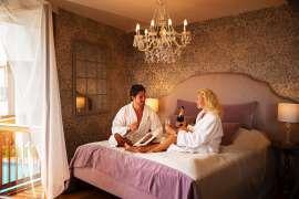Ein junges Paar in Bademänteln geniesst auf dem Bett Sekt und Nachereien im Romantikzimmer