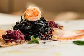Ein raffinierte angerichteter Meeresfrüchteteller, im ZTentrum ein Knäuel schwarze Nudeln, gekrönt von einem zartrosa Scampi