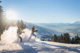 Schneeschuhwandern vor traumhafter Kulisse mit Winterwald und verschneiten Berggipfeln