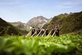 Tradition im Stubaital: 6 Alphornbläser auf einer grünen Wiese, dahinter Berggipfel