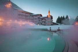 Verschneites Posthotel Achenkirch mit dampfendem Turm-Pool
