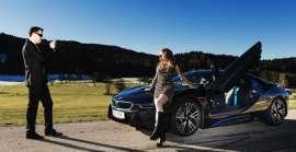 Winzers Autoverleih - sie lehnt an einem eleganten BMW i8, er fotografiert