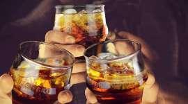 3 Hände stossen mit jeweils einem Glas mit Americano auf Eiswürfeln an