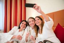 3 junge Frauen in weissen Bademänteln machen ein Gruppen-Selfie