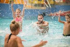 Eine Familie im Schwimmbad hat Spass, es wird gespritzt