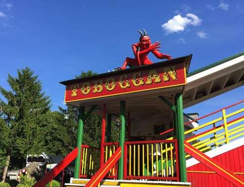 Eingang zum Tobogan, auf dessen Dach sitzt eine roter Teufel der eine lange Nase dreht