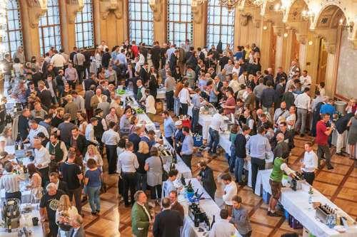 Zahlreiche Menschen umgeben die Tische der Winzer im Palais Ferstl und verkosten