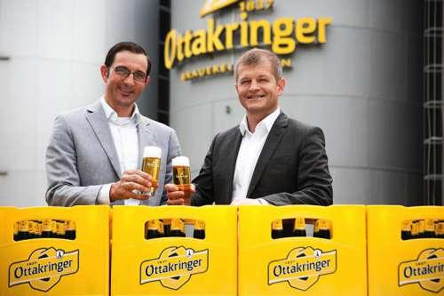 Tobias Frank und Matthias Ortner stossen hinter einer halbhohen Wand aus Ottakringer Kisten mit Bier an