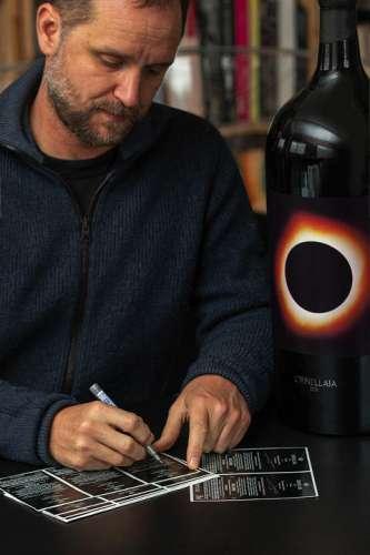 Tomas Saraceno signiert Ornellaia Etiketten, im VOrdergrund eine Großflasche im von ihm entworfenen Design