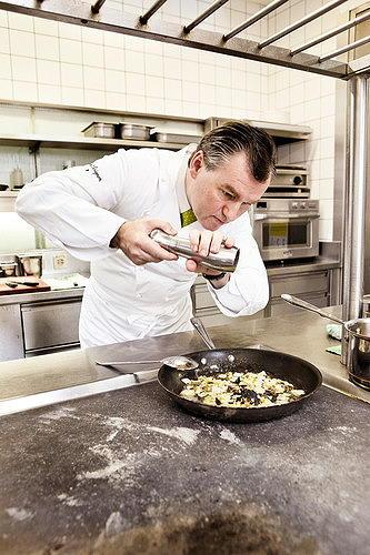 Toni Mörwald in der Küche, mit der Pfeffermühle über einer Casserolle