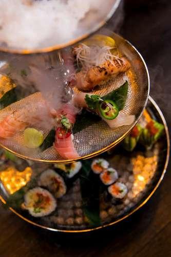 Zwei runde Platten mit kreativem Sushi in der Etagere, darüber eine Platte mit Trockeneis