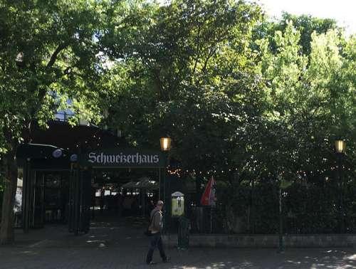 Zwischen grünen Bäumen der Eingang zum Schweizerhaus mit Schild